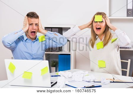 Businessman and businesswoman are having too much work to do.