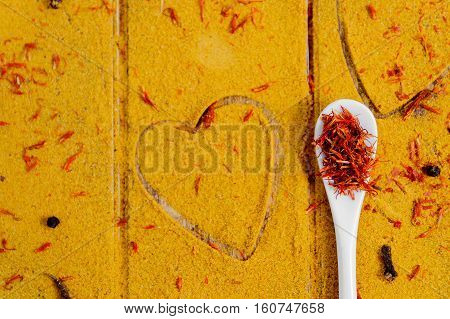 Heart Of Spices And Seasonings. White Spoon With Saffron On Curry Background.  Various  Selection. C