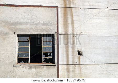 Broken stained window surface of a partially demolished factory