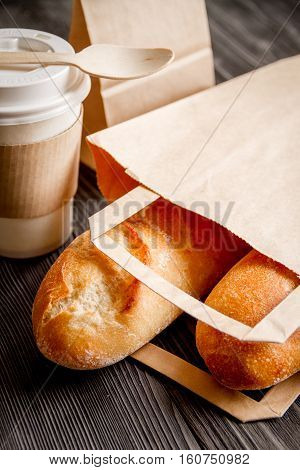 cup of coffee and bread in paper bag on wooden background
