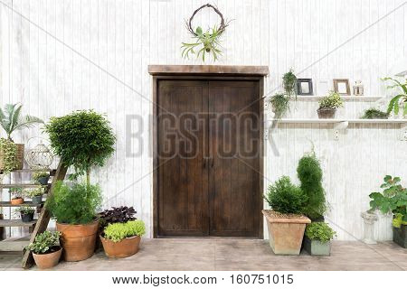 Front wood door and garden decor in white cosy house or cottage. Exterior of house.