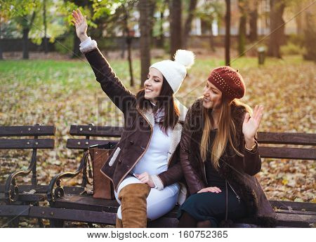 Fun stylish young women waving a greeting with happy vivacious smile as they relax sitting together on a bench in an autumn park