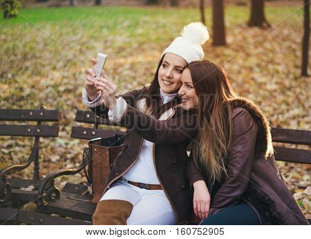 Two attractive trendy girlfriends taking a selfie posing close together on a bench in an autumn park smiling happily for the camera