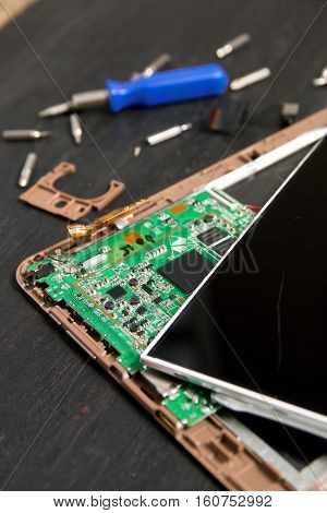 Process Of Pc Tablet Device Repair Near Screwdriver And Bit On Black Wooden Background. Disassembled