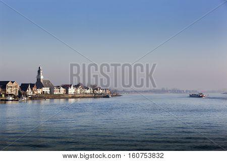 Village Lekkerkerk near the river Lek in the Netherlands. An industrial ship is passing by.