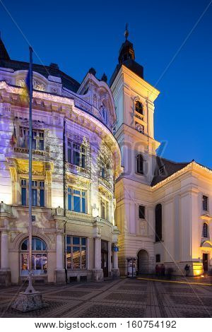 SIBIU, ROMANIA - NOVEMBER 26th, 2016 - Twilight image of the City Hall and Holy Trinity Roman-Catholic church in Sibiu with architectural lights projecting Christmas images on the walls.