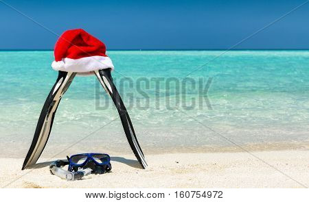 Fins and mask with Christmas hat on a tropical beach