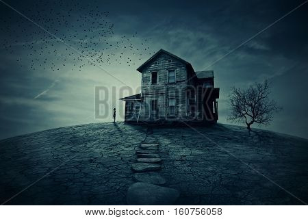 Young man stand at the corner of a ravaged house looking far away for someone. A ghost desolated house with a dry land and tree.