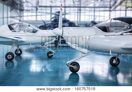 two white sport planes in a hangar