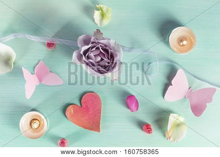 A Valentine day card with a rose flower, paper butterflies, sweets, candles, beads, petals, a little cutout heart, and copyspace, slightly toned
