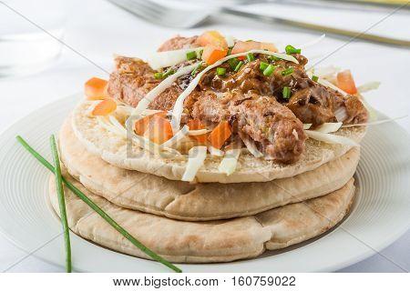 Shish kofte (kofta kebab) street food with vegetables and herbs on pita bread