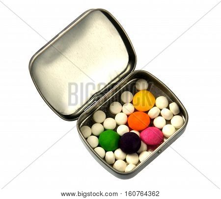 Metallic silver pillbox with white and color pills isolated on white background