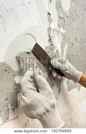 hands scraping off old wet wallpaper with spatula
