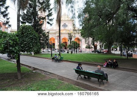 Salta Argentina - 21 January 2011: People sitting on the benches of the central park in front of the cathedral of Salta on northen Argentina