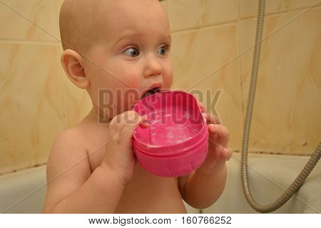surprised little baby is playing in the bath with soap-dish. funny cute baby taking a bath with toys. he likes to splash in the water. little smiling baby. his face lit with happiness. beautiful baby bathing and playing in the water