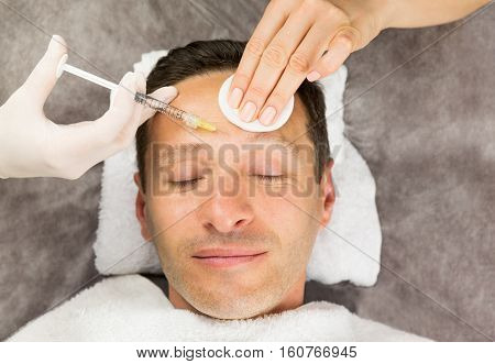 Face of laying man hands of beautician with a syringe and sponge horisontal