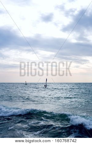 Group of windsurfers on boards in wavy sea. Lifestyle and sport completition concept. Group of people. Fun and leisure activity. Vertical composition.