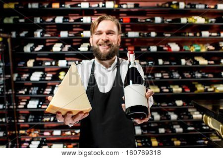 Portrait of a sommelier in uniform with parmegiano cheese and bottle of wine at the restaurant or supermarket. Choosing wine according to the type of cheese. Bottle with empty label to copy paste
