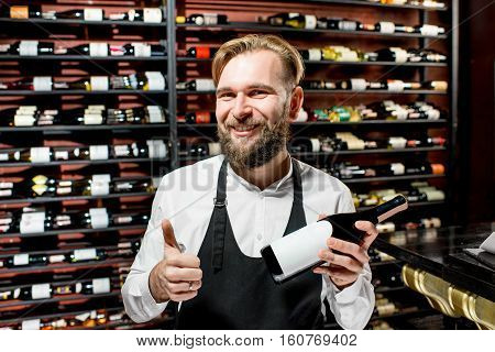 Portrait of a happy sommelier in front of the shelves with wine bottles at the luxury supermarket or restaurant