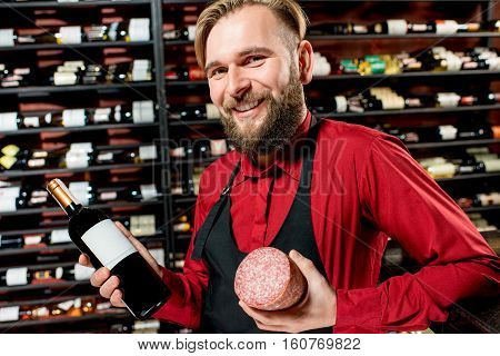Portrait of a seller or sommelier with wine bottle and salamy sausage at the luxury supermarket or restaurant. Choosing wine according to the type of meal. Bottle with empty label to copy paste
