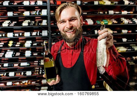 Portrait of a seller or sommelier with wine bottle and trout fish at the luxury supermarket or restaurant. Choosing wine according to the type of fish. Bottle with empty label to copy paste