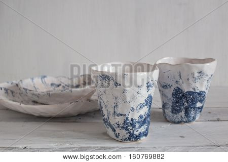 set of white pottery with ink blue spots white pottery on a light background bowl and cup from clayink blue spots.