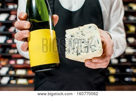 Food seller holding a bottle of white wine and a pieace of blue cheese. Choosing wine according to the type of cheese. Bottle with empty label to copy paste