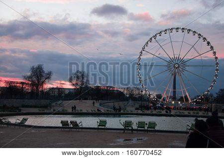 Ferris wheel in Paris. Roue de Paris. View from The Tuileries Garden. Sunset in Le jardin des Tuileries