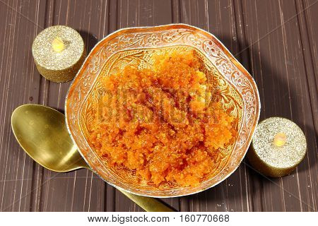 Gajar halwa or carrot dessert in a bowl on a moody dark background copy space