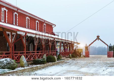 Lithuanian countryside snowy winter. Baltic rustic architecture with wooden houses and restaurant of traditional Lithuanian cuisine Griezpelkiai. Republic of Lithuania European Union