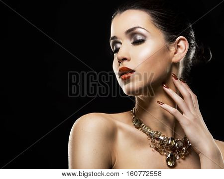 romantic woman with golden makeup and nailpolish. Big gold fashion necklace. Black isolated background.