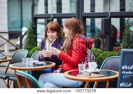 Two Cheerful Young Girls In A Parisian Street Cafe