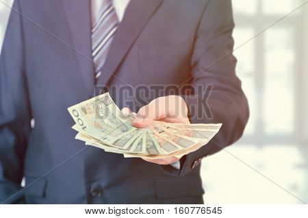 Range of Polish banknotes in hand. businessman giving money loan polish zloty pln hand concept