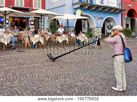 Alphorn Player Entertaining People At Restaurant Of Ascona