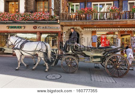 Horse Vehicle And Tourists At City Center Of Zermatt