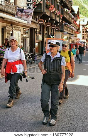 Tourists Doing Nordic Walking At City Center Zermatt