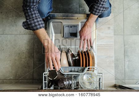 The man pushed the dirty dishes in the dishwashing machine.