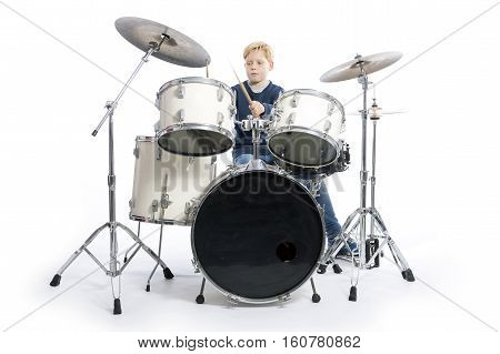 young blond boy drums behind drum kit against white background in studio