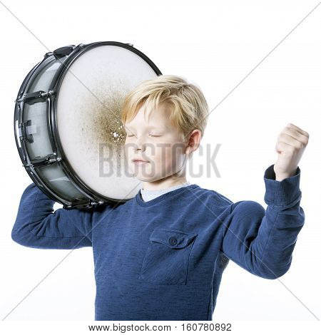 young blond boy with drum against white background in studio shows muscle and closed eyes