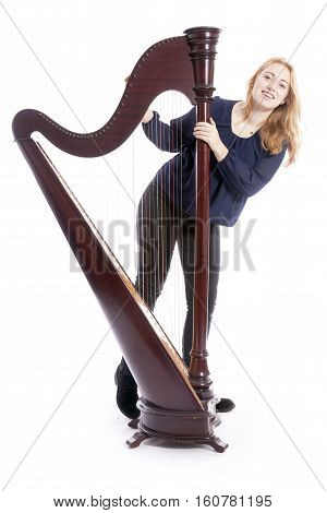 red blond teenage girl with harp against white studio background