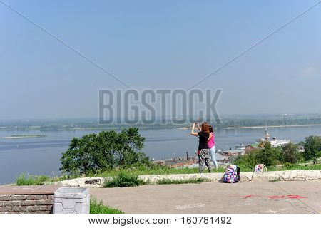 Nizhny Novgorod Russia. - July 28.2016. Young girls photographers photographed view of the intersection of the rivers Oka and Volga from the high bank on Zalomova street