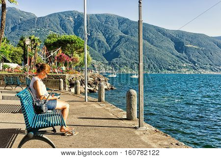 Ascona Switzerland - August 23 2016: Woman sitting on the bench at the embankment of the expensive resort in Ascona on Lake Maggiore Ticino canton Switzerland.
