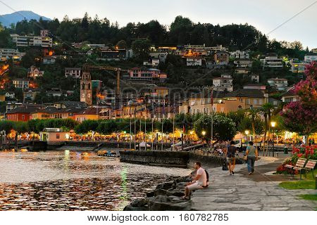 Ascona Switzerland - August 23 2016: Quay of the luxurious resort in Ascona on Lake Maggiore in Ticino canton in Switzerland. Afret sunset. People on the background