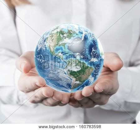 Close up of a woman in a white blouse is holding a planet in her hands. Concept of a small world.