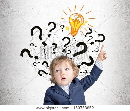 Portrait of an adorable baby boy in a blue suit pointing upwards while standing near a bright light bulb sketch with question marks drawn on a concrete wall