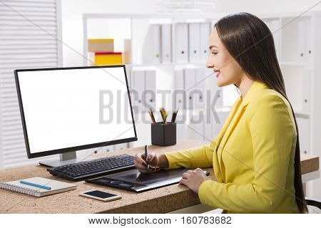 Side view of a woman in yellow jacket drawing on a pad near her computer with a large monitor. Smartphone on the table. Mock up