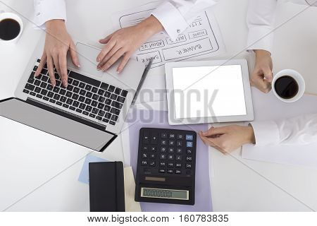 Top view of two pairs of women's hands. One is typing on her laptop keyboard. Her colleague is having coffee. Mock up