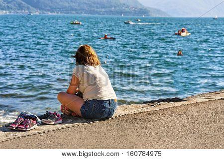 Woman Sitting On Bench In Ascona Resort At Ticino Switzerland