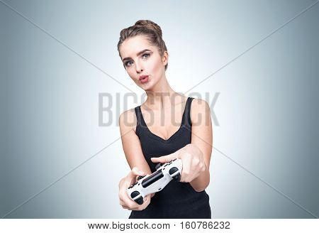 Geeky girl in a black tank top is holding a video game controller and enjoying her spare time while standing near a gray wall. Mock up