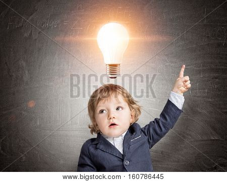 Little kid standing with his finger pointing upwards near a blackboard with a big glowing light bulb sketch